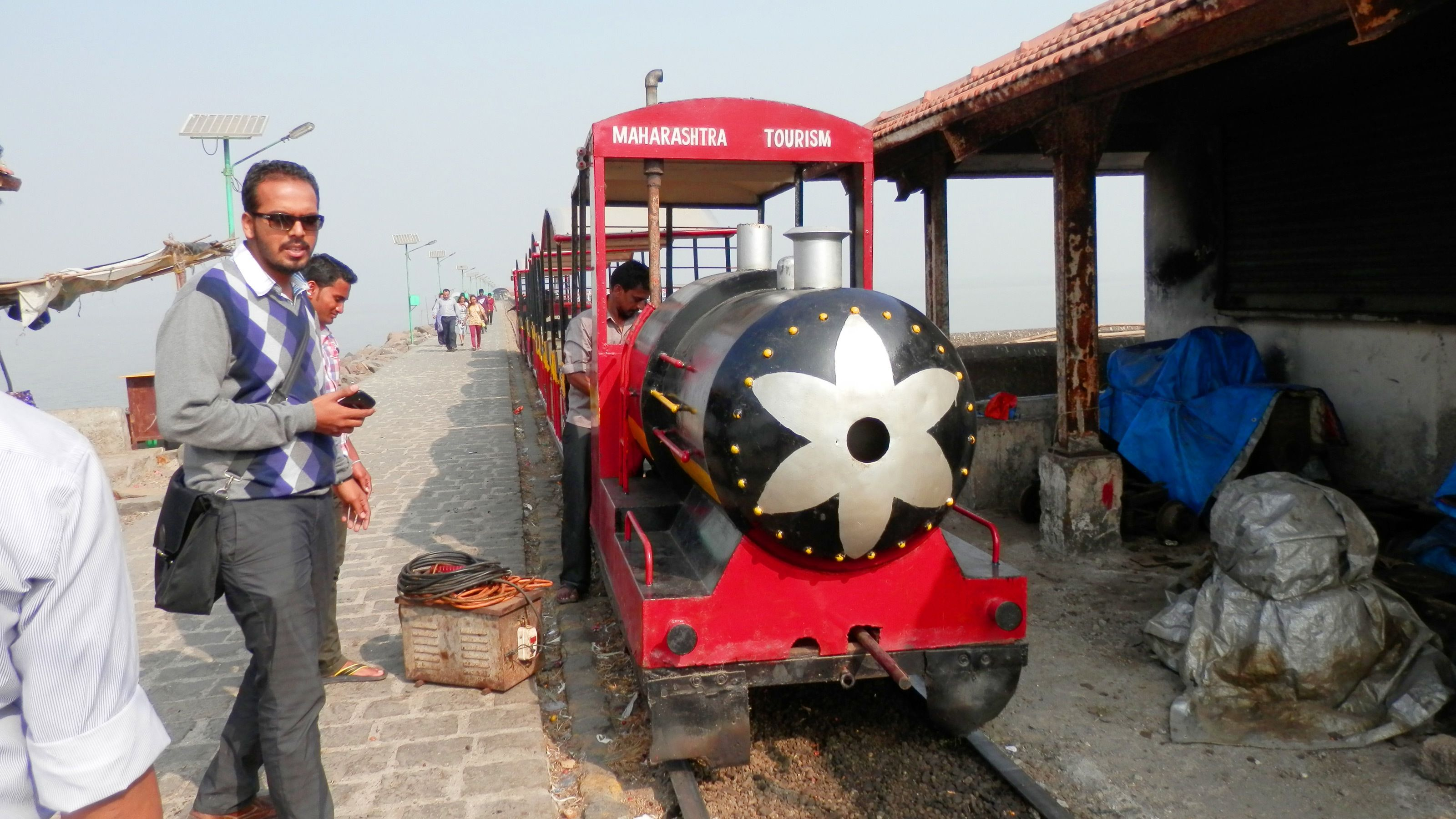a train pulling in to a station at mumbai harbor