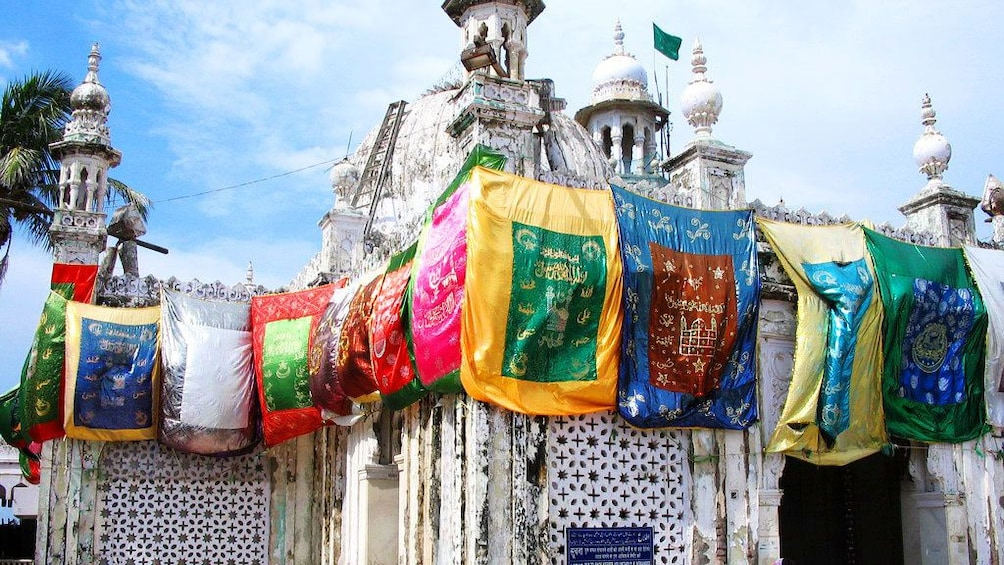 Show item 2 of 6. Colorful prayer flags cover a place of worship in Mumbai