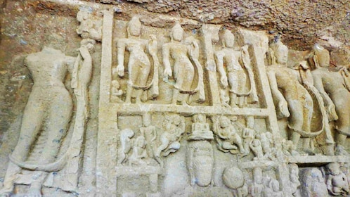 Remains of a relief sculpture depicting several human figures at the Kanheri Caves