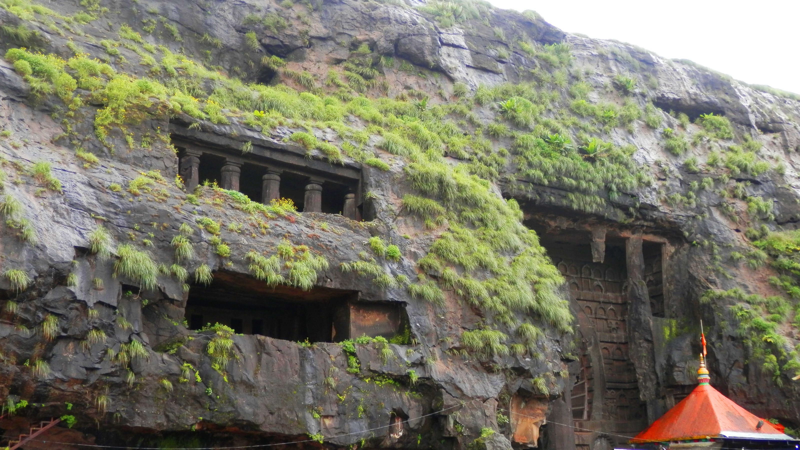 Remains of a temple peak through moss covered cliff faces at the Bhaja caves