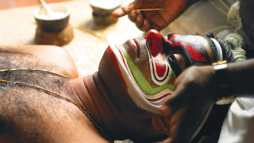 Man getting his face painted in preparation for the Kathakali Dance Show in Kochi