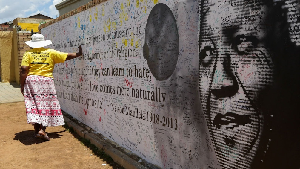 Show item 1 of 9. Woman with her hand on a Nelson Mandela mural in Soweto, South Africa