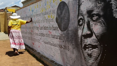 Woman with her hand on a Nelson Mandela mural in Soweto, South Africa