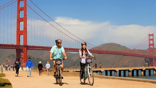 Two people riding a bike next to the Golden Gate Bridge