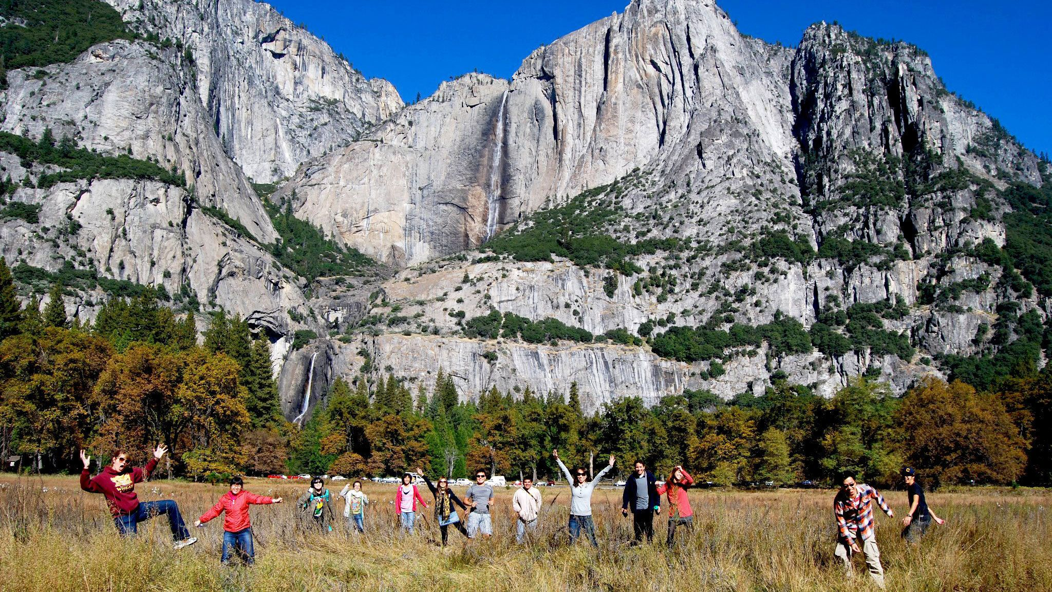 Group in a field in front of mountain at Yosemite National Park