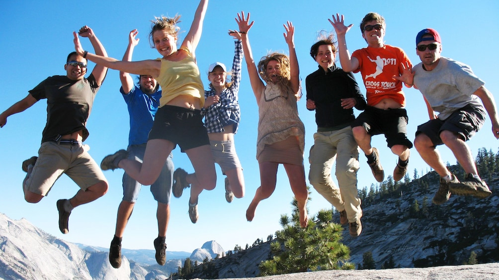 Show item 4 of 10. Group of people jumping in the air at Yosemite National Park