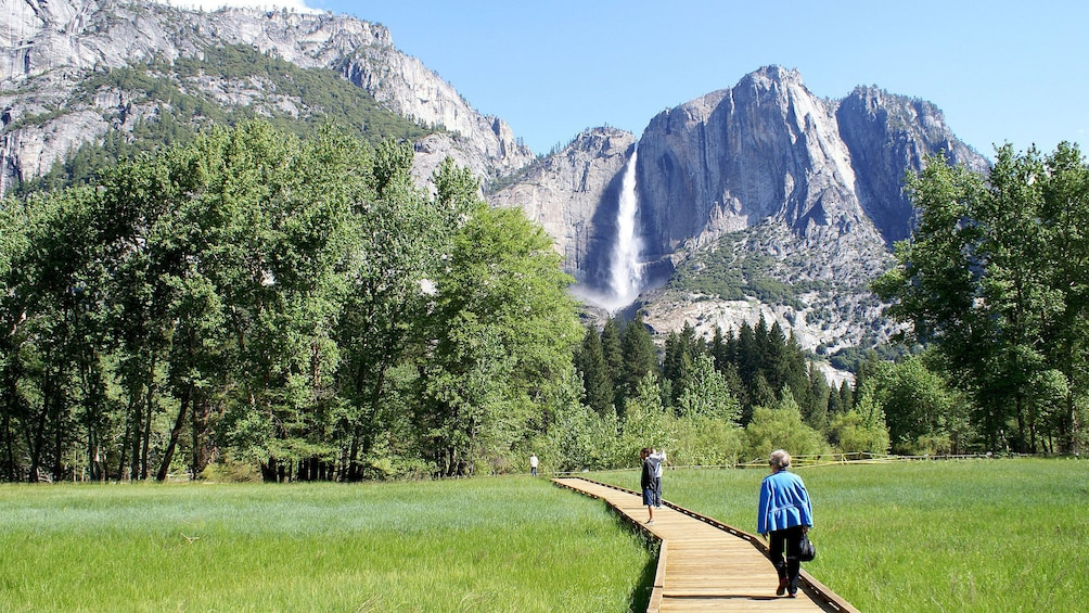 Indlæs billede 2 af 10. People walking on Sentinel Meadow boardwalk with waterfall in the distance at Yosemite National Park