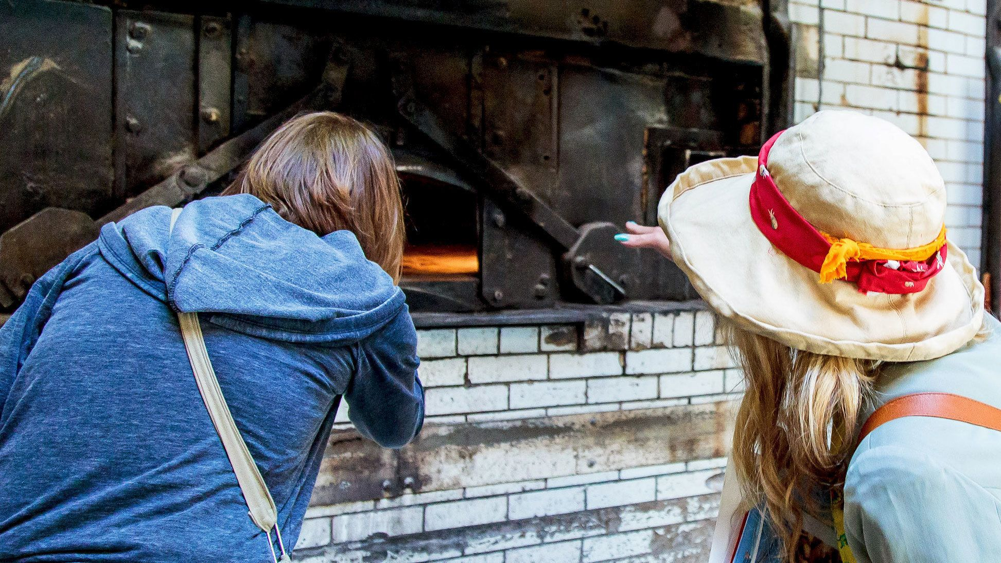 Women looking in pizza oven in San Francisco
