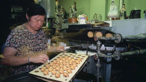 Woman making fortune cookies in Chinatown San Francisco