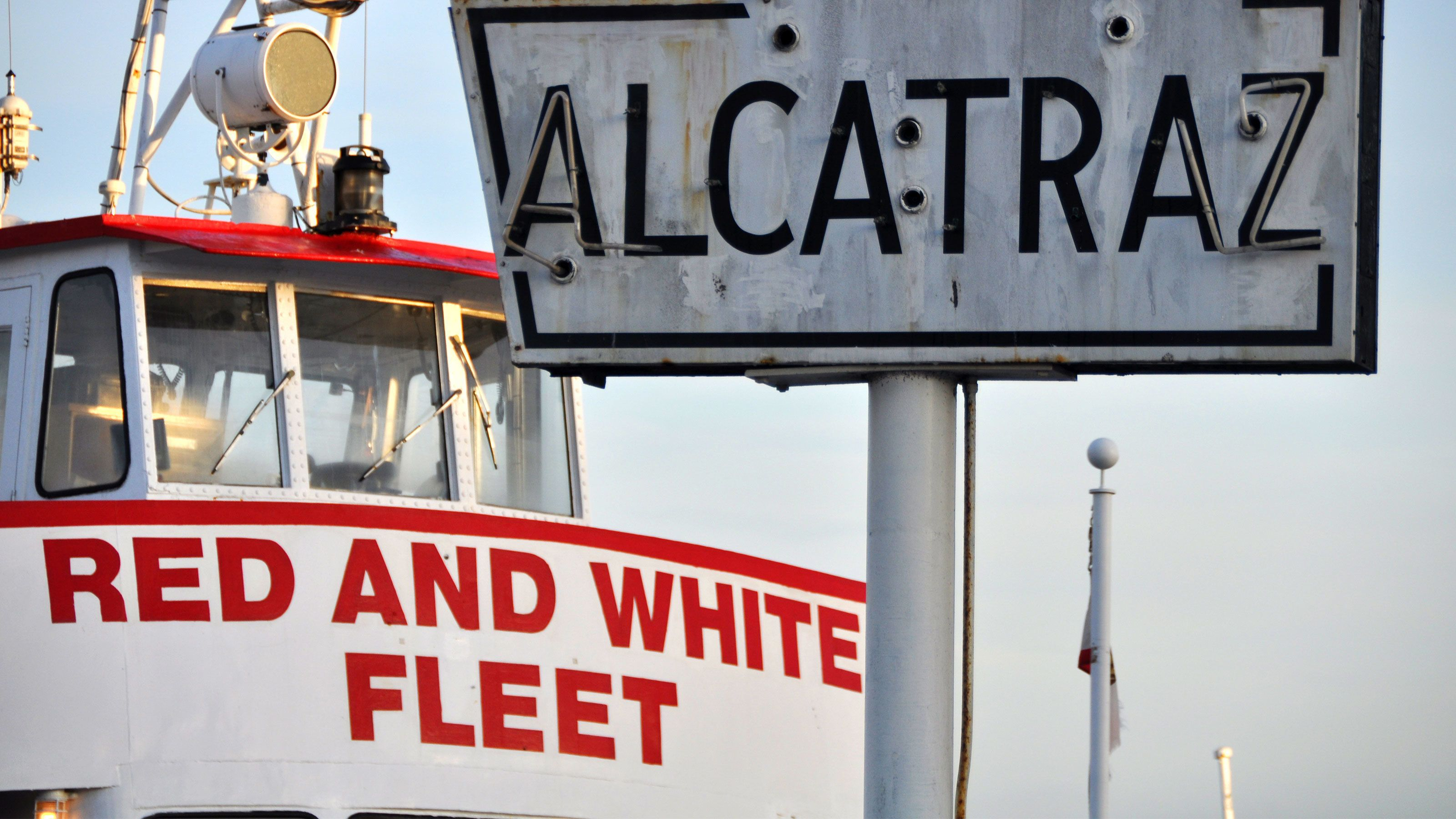 Weathered Alcatraz sign with cruise boat behind in San Francisco