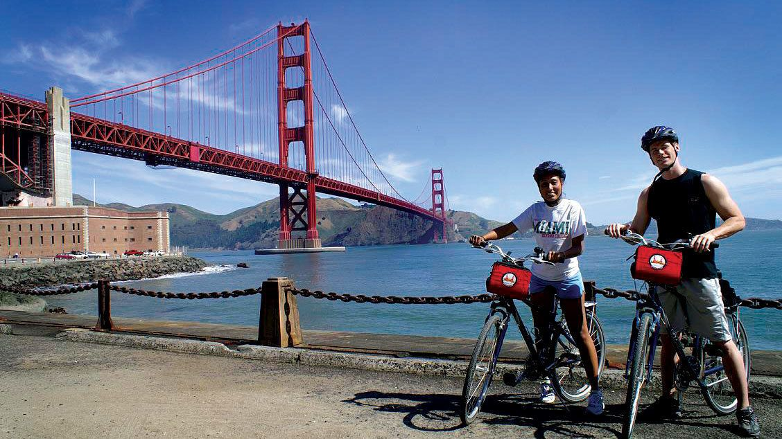 Bicycling couple with the Golden Gate Bridge in San Francisco