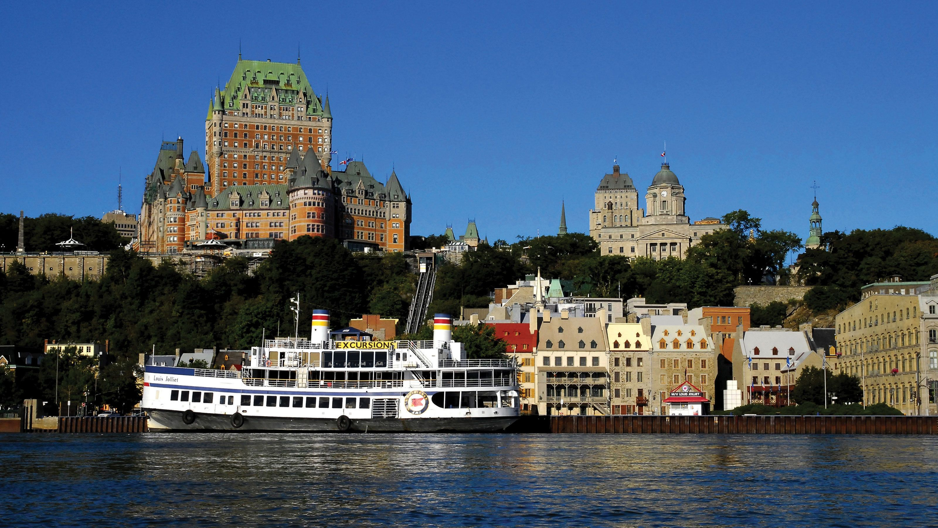 Boat passing in front of old buildings on the waterfront in Quebec City.