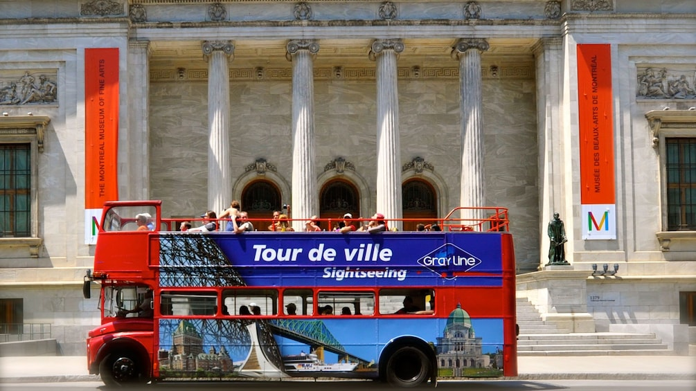 Show item 3 of 5. Red Hop On Hop off double-decker bus in front of the Montreal Museum of Fine Arts