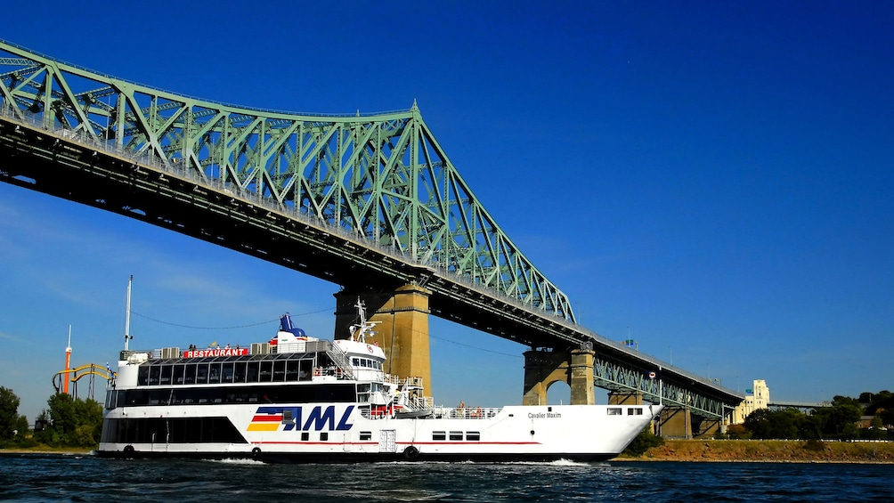 Show item 5 of 5. Sightseeing boat passes under the The Jacques Cartier Bridge on the St. Lawrence River