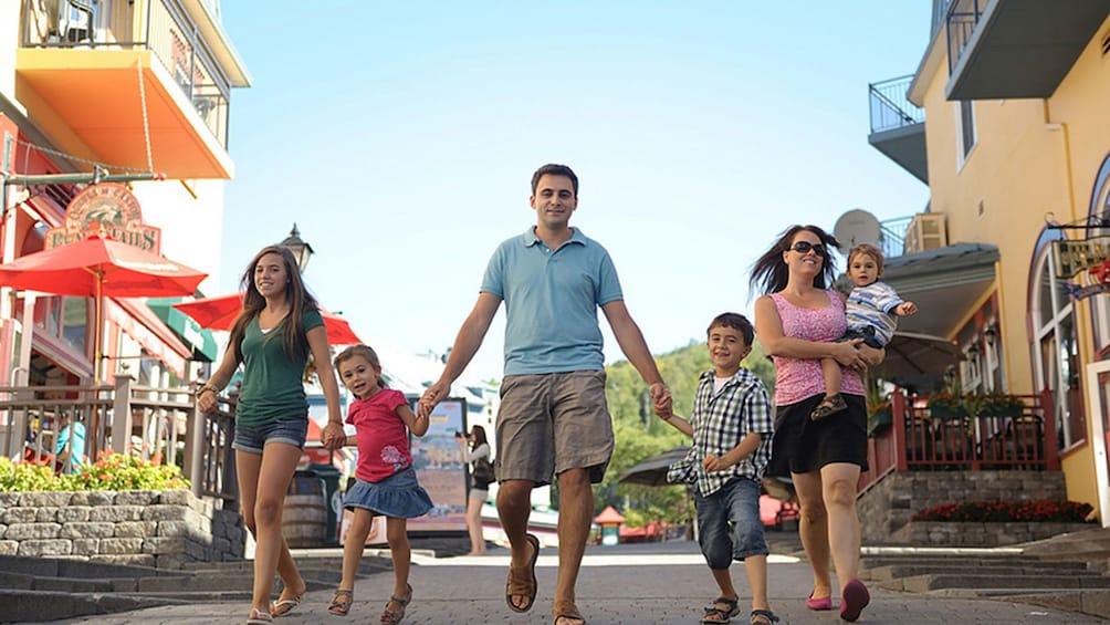 Foto 3 von 5 laden Family walking down the street in the village of Mont-Tremblant