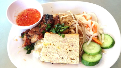 Rice plate with meet and vegetables and fish sauce on the street food tour of Ho Chi Minh City