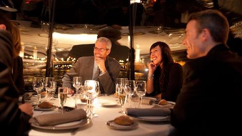 Friends enjoying a dinner cruise along the Seine