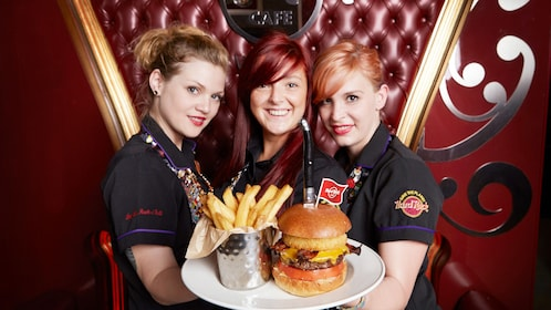 Trio of waitresses holding a plate with a giant hamburger at the Hard Rock Cafe in Vienna