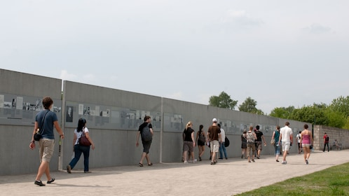 People walk beside a memorial wall at Sachsenhausen
