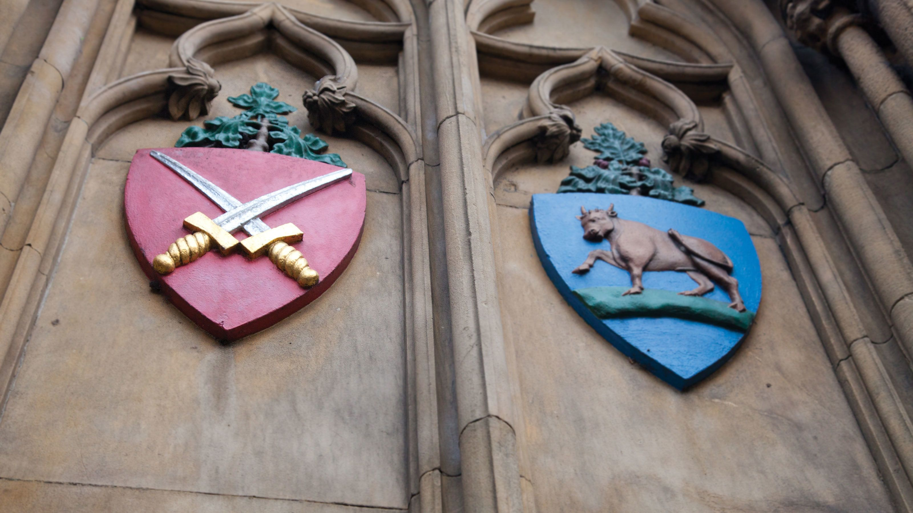 wooden family crests upon stone wall at Oxford