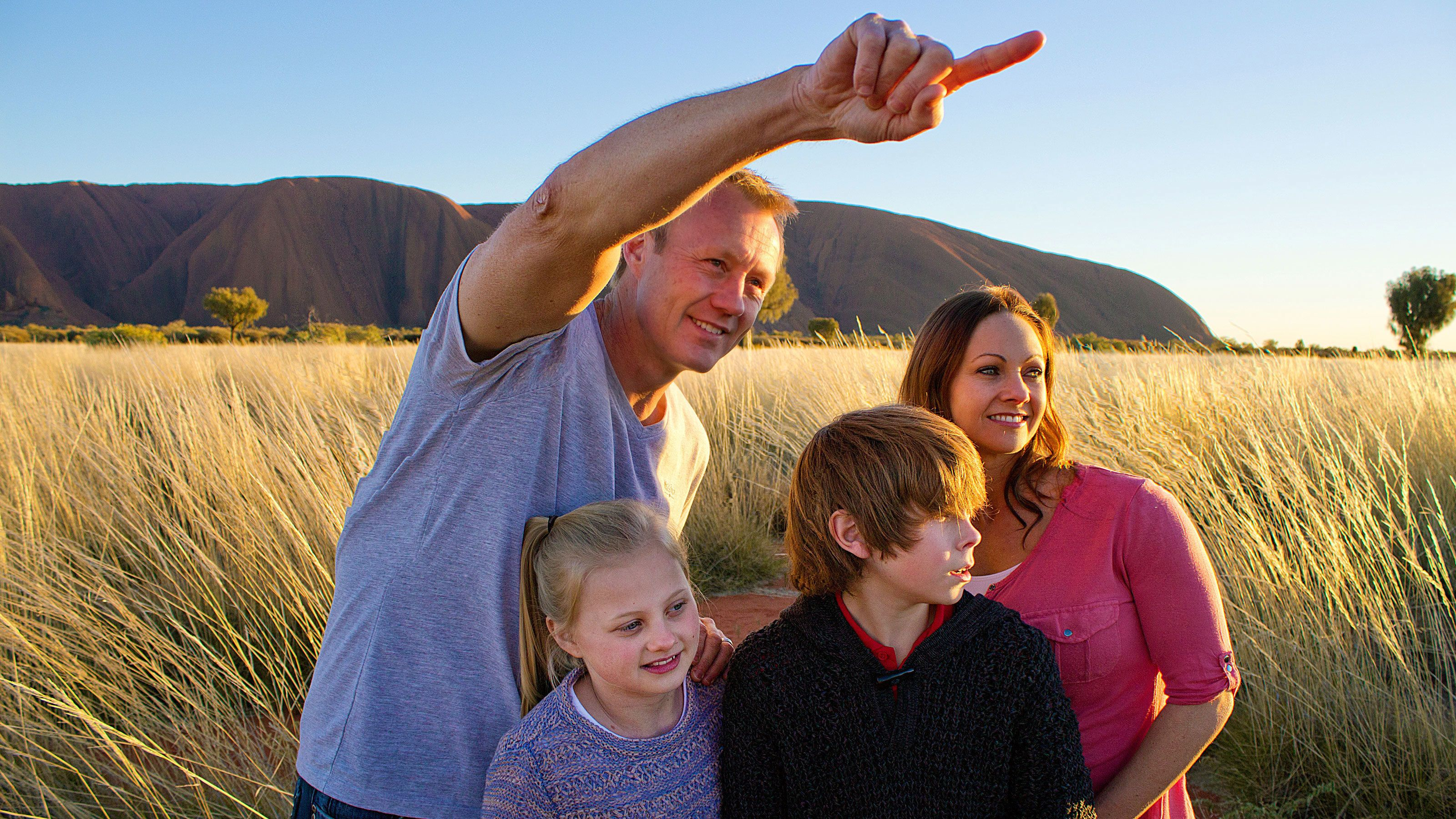 Family in a field at Uluru National Park in Central Australia