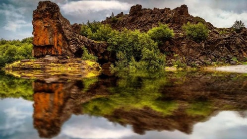 Colorful rocks and trees reflected in a still lake in Reykjavik