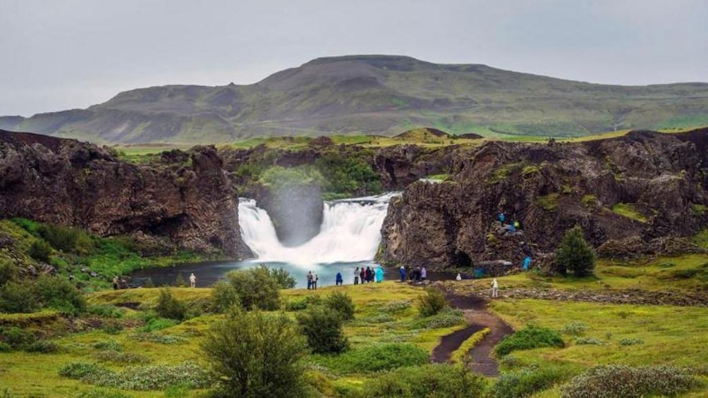 Tour group standing a a waterfall and pool in Reykjavik