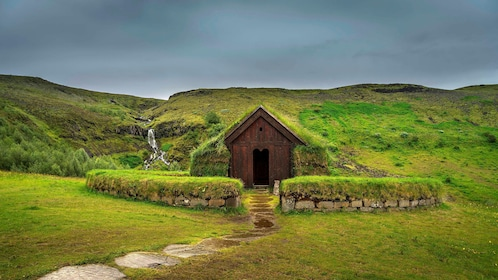 Grass covered house and surrounding hills in Reykjavik