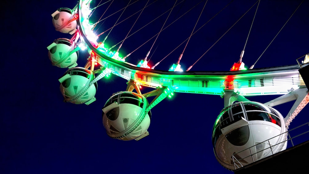 Show item 5 of 5. Close up of The High Roller Observation Wheel at night with neon lights in Las Vegas
