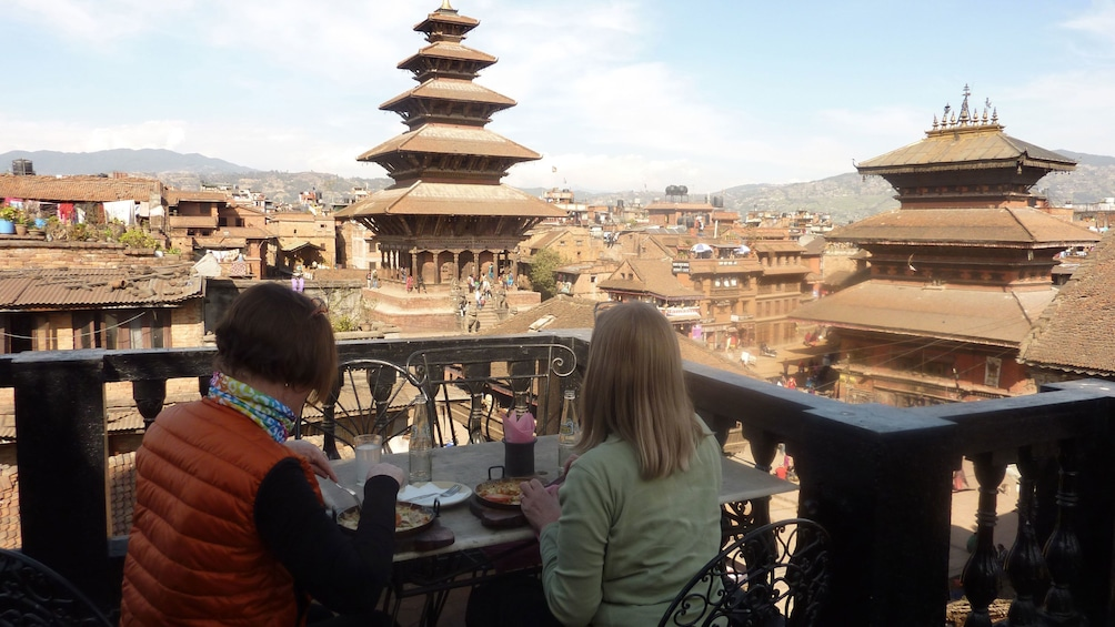 Show item 4 of 10. Two people enjoy lunch on a balcony with a view of Bhaktapur