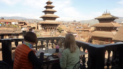 Two people enjoy lunch on a balcony with a view of Bhaktapur