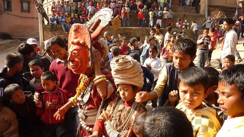 People dressed for a festival make their way down a street in Patan