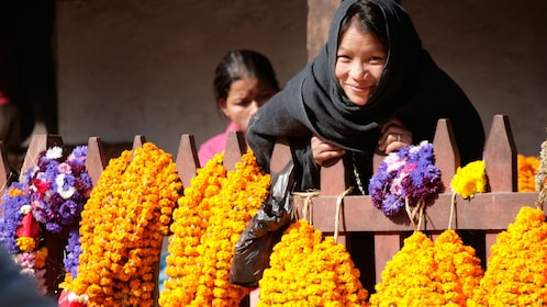 A woman in Bhaktapur surrounded by colorful flowers
