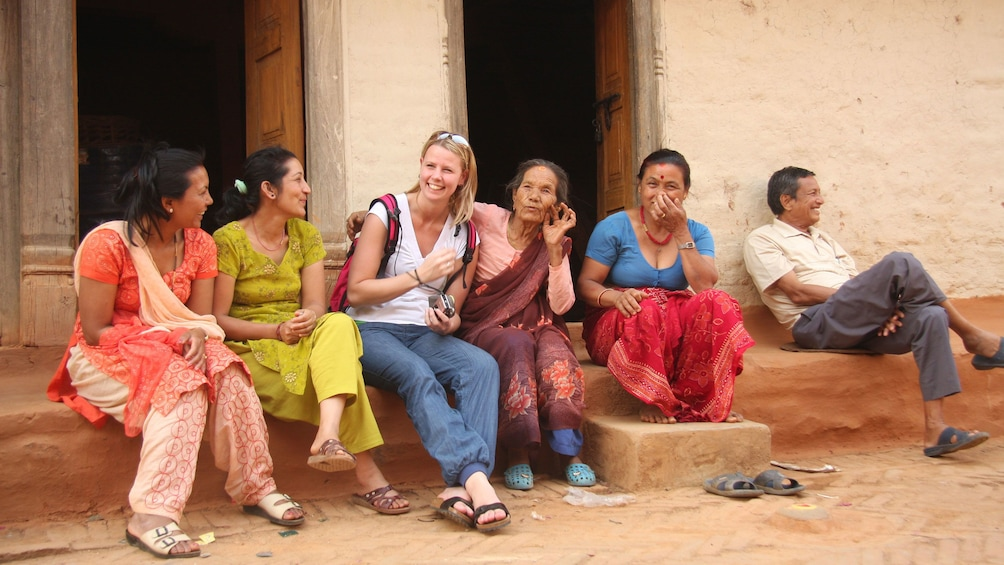 Show item 2 of 10. A woman talking with locals in Bhaktapur