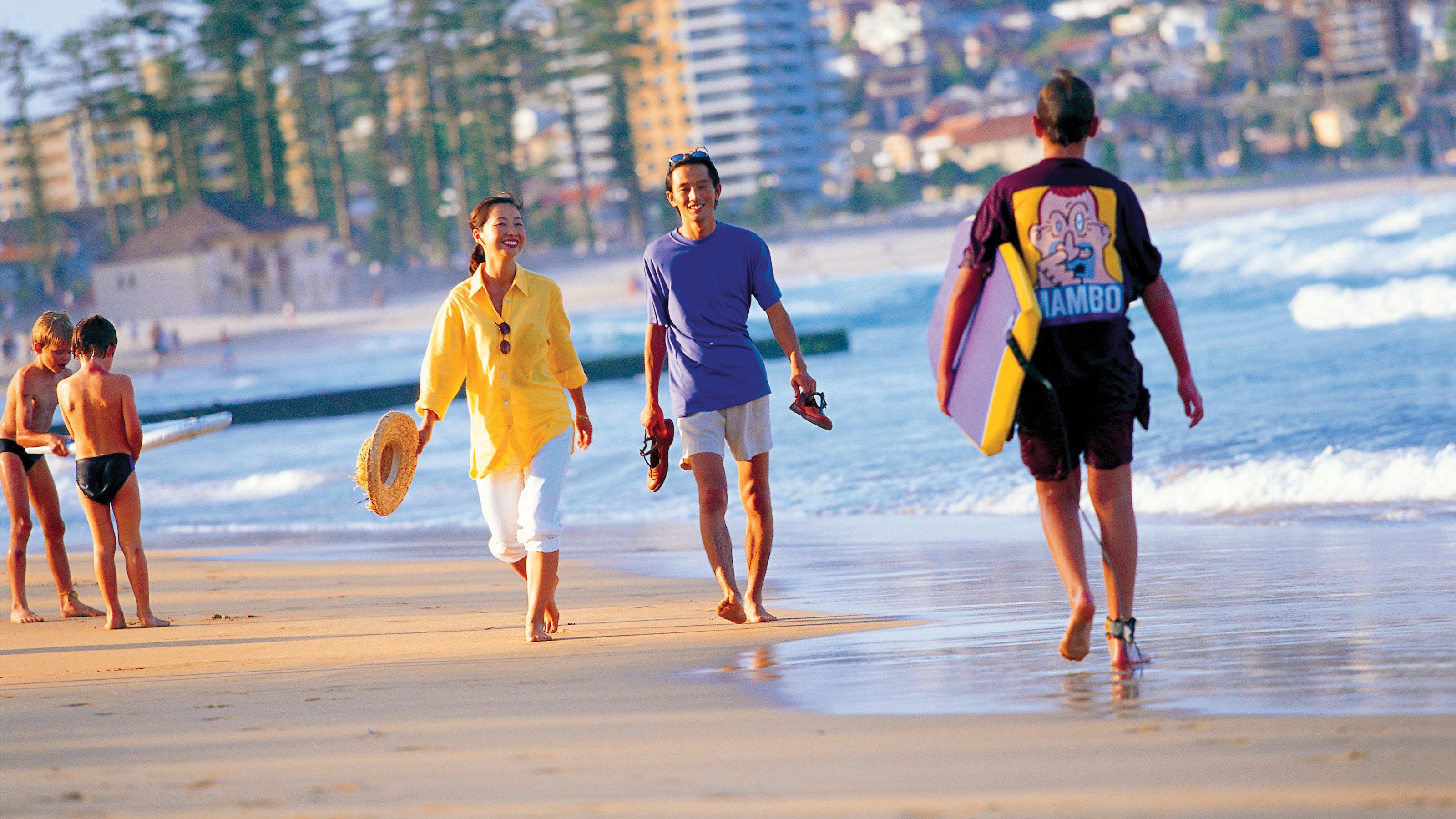 People walking on the shores of a beach in Australia on a beautiful sunny day