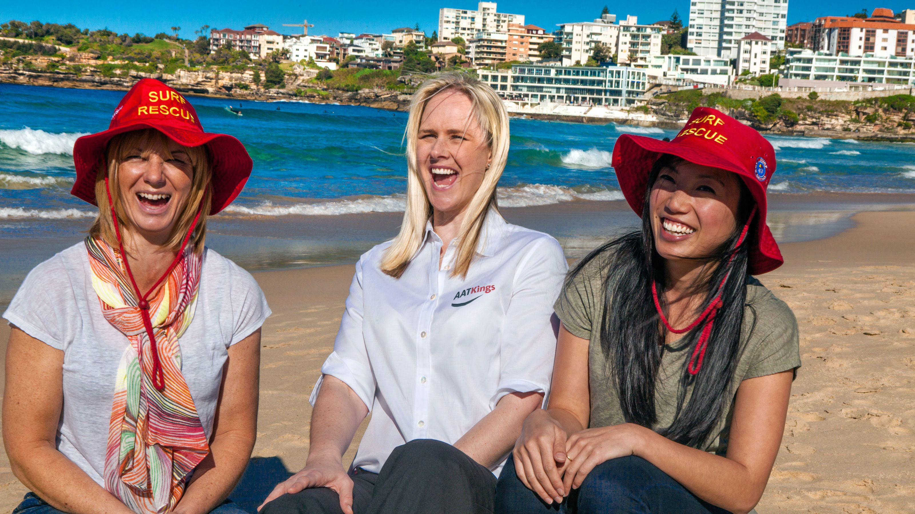 Three ladies smiling as they sit on the sand at the beach in Australia