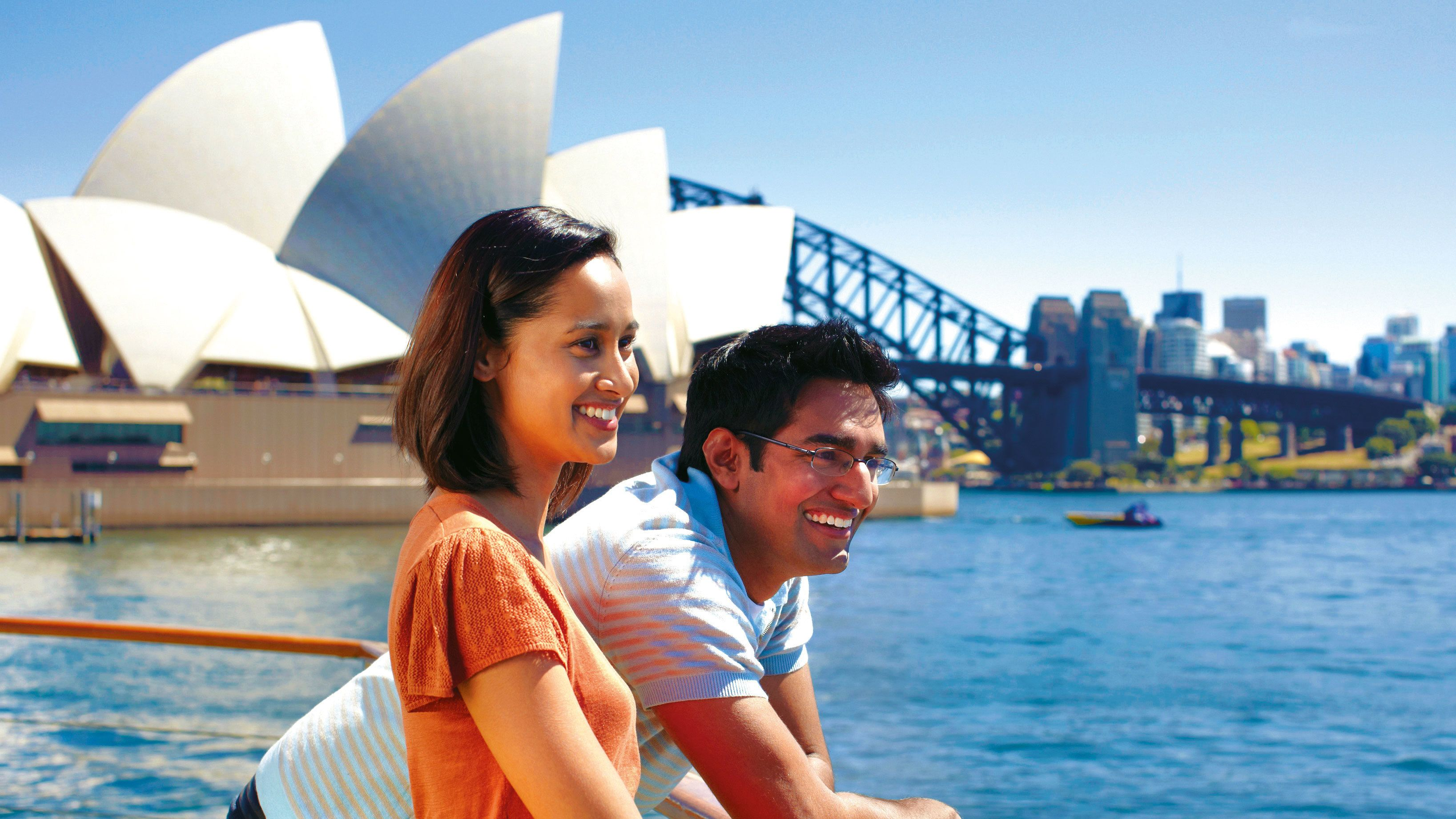 Couple smiling on the Sydney Harbour with the Sydney Opera House in the background on a sunny day