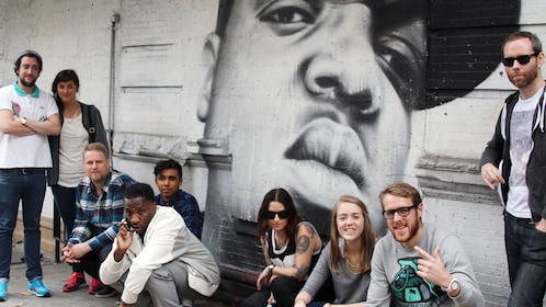 Group in front of graffiti portrait in New York