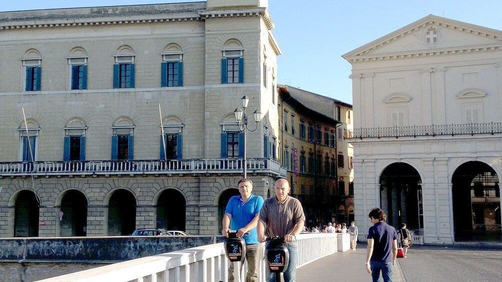 Show item 4 of 9. Seqway riding pair on a bridge in Pisa