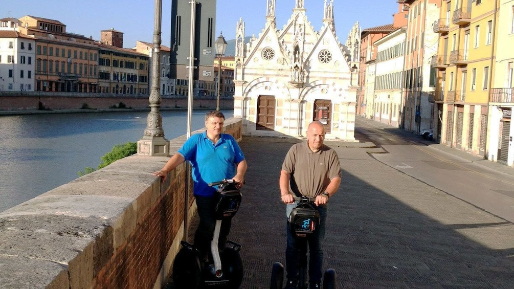 Show item 5 of 9. Segway riding men next to the river in Pisa