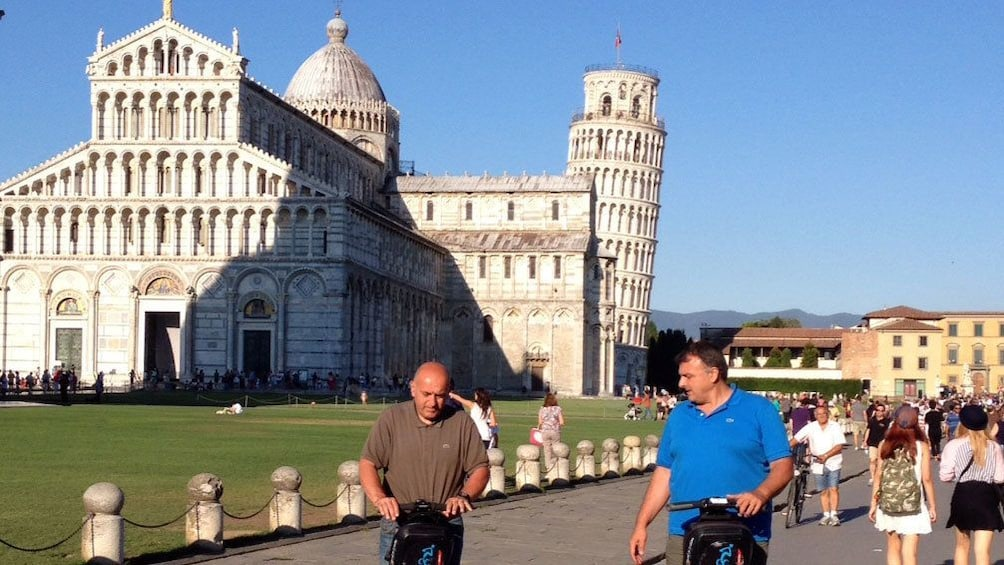 Show item 2 of 9. Segway riding men in the Square of Miracles with the Leaning Tower in the background in Pisa