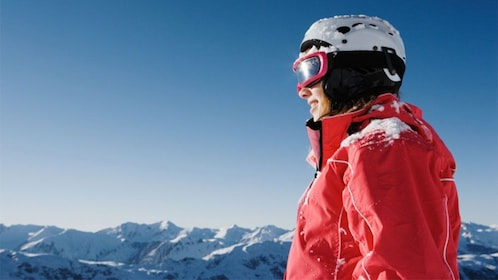 Skiing woman looks out at the surrounding mountains in Winter Park