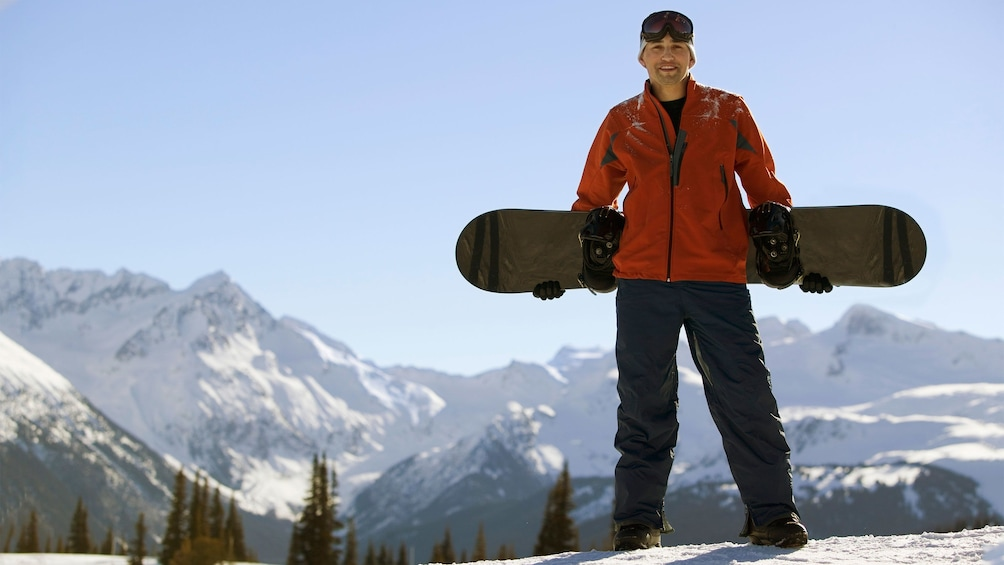 Show item 5 of 5. Man enjoying the view of the mountains before snowboarding down the slopes
