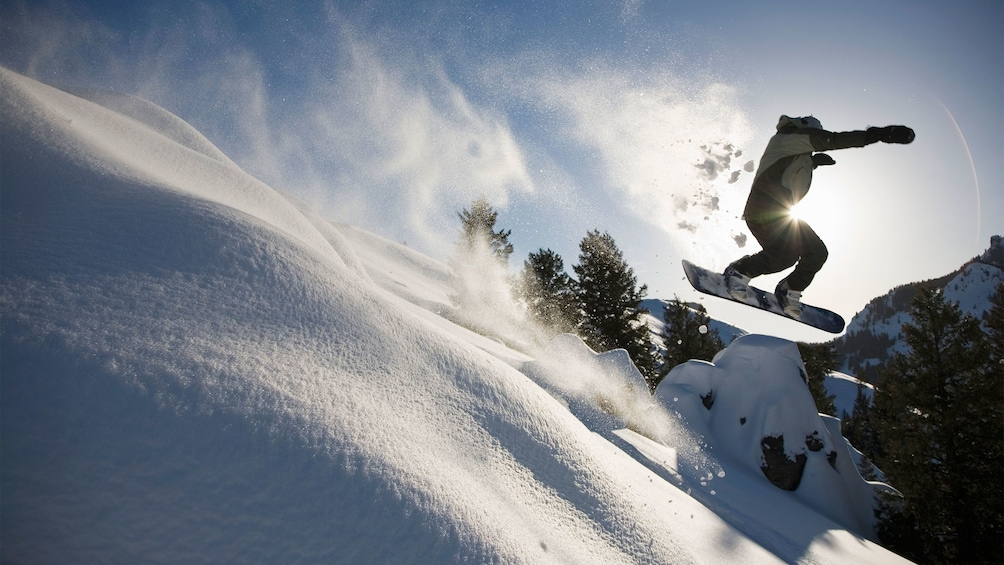 Show item 1 of 5. Catching air while snowboarding down the mountain