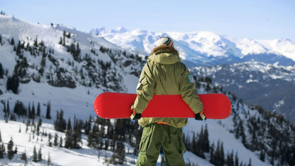 Show item 3 of 5. Snowboarder enjoying views of the Canadian Rockies before descending the slopes