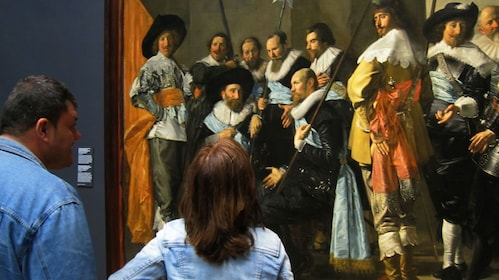 Man and woman observing painting at museum in Amsterdam