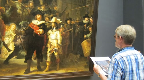 Man observing painting at museum in Amsterdam