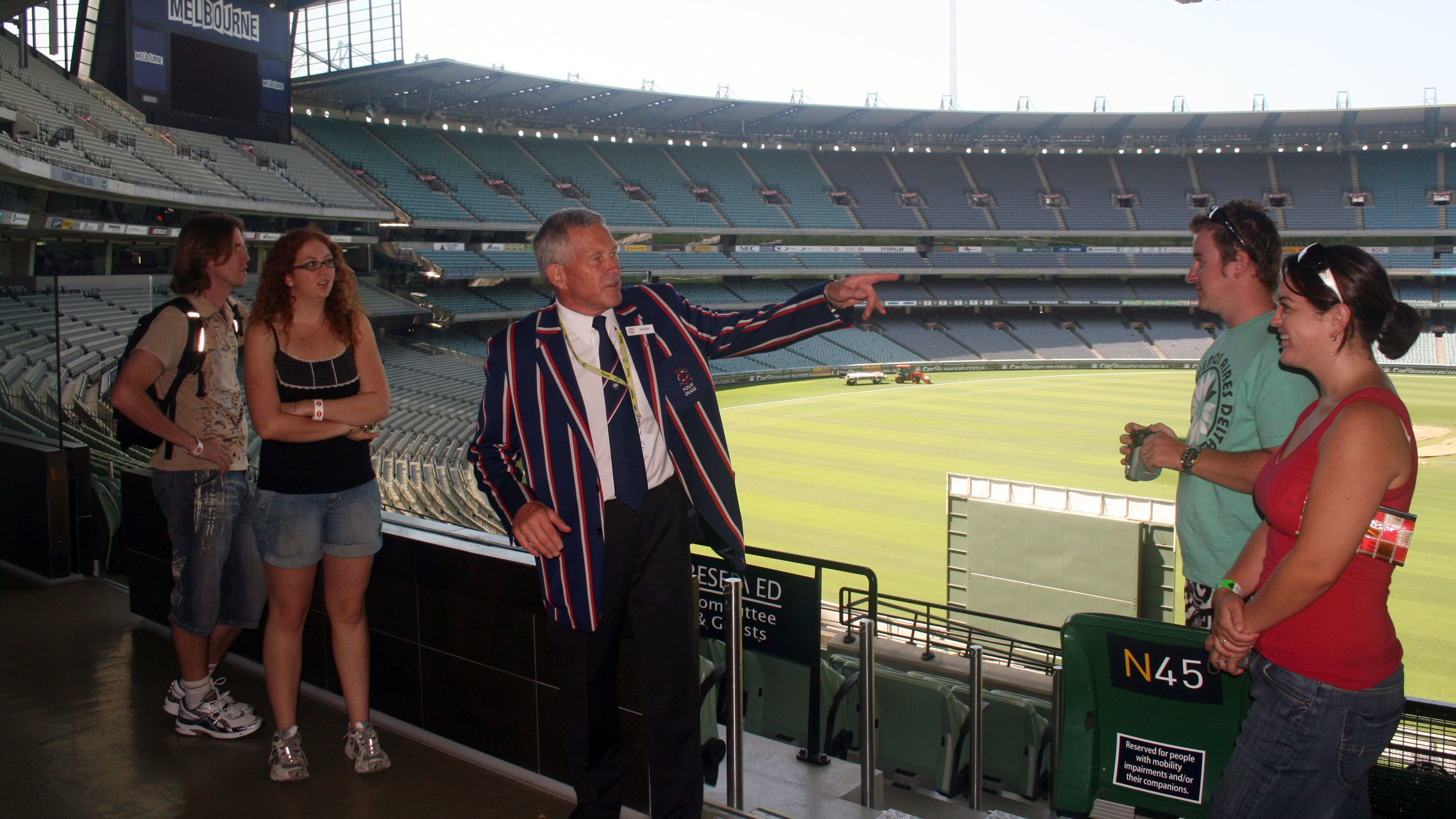 Tour guide talking to group at stadium in Melbourne