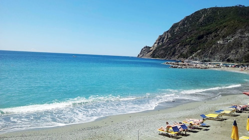 Beachgoers on chaise lounges along a sandy beach in the Cinque Terre