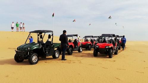 people walk around sand buggies parked on sand dunes.